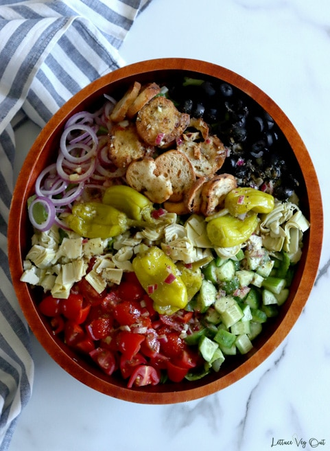 Top view of large oval dark wood bowl filled with un-tossed Italian salad (tomato, cucumber, artichoke, black olives, croutons, red onion, pepperoncini peppers). White-grey marble background with white blue striped towel along left edge of image.