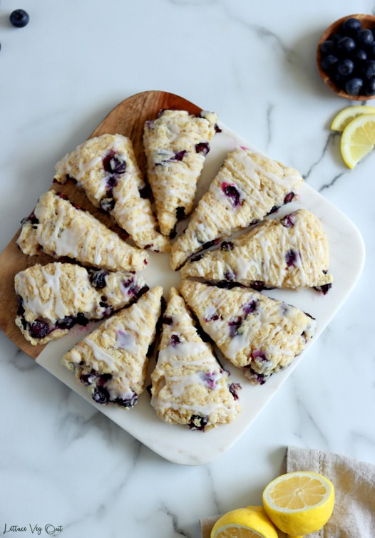 Top view of triangle-shaped scones crating a full circle on a half wood half marble board. Scones topped with a drizzle of white icing. Lemons in bottom right corner and blueberries with lemon slices in top left corner.