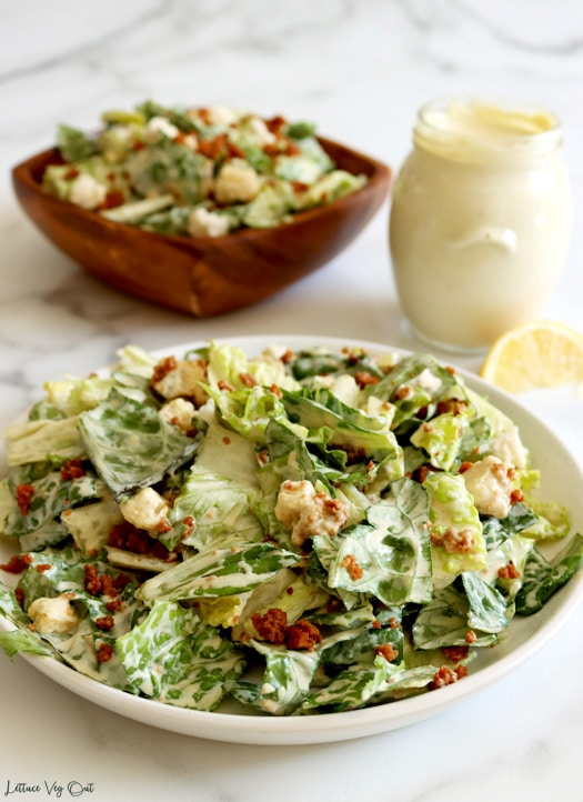 Close up of a plate of tossed Caesar salad (chopped Romaine lettuce, bacon bits and croutons with cream dressing). Blurred in the back is a jar of dressing with a lemon wedge and a square wood bowl filled with salad.