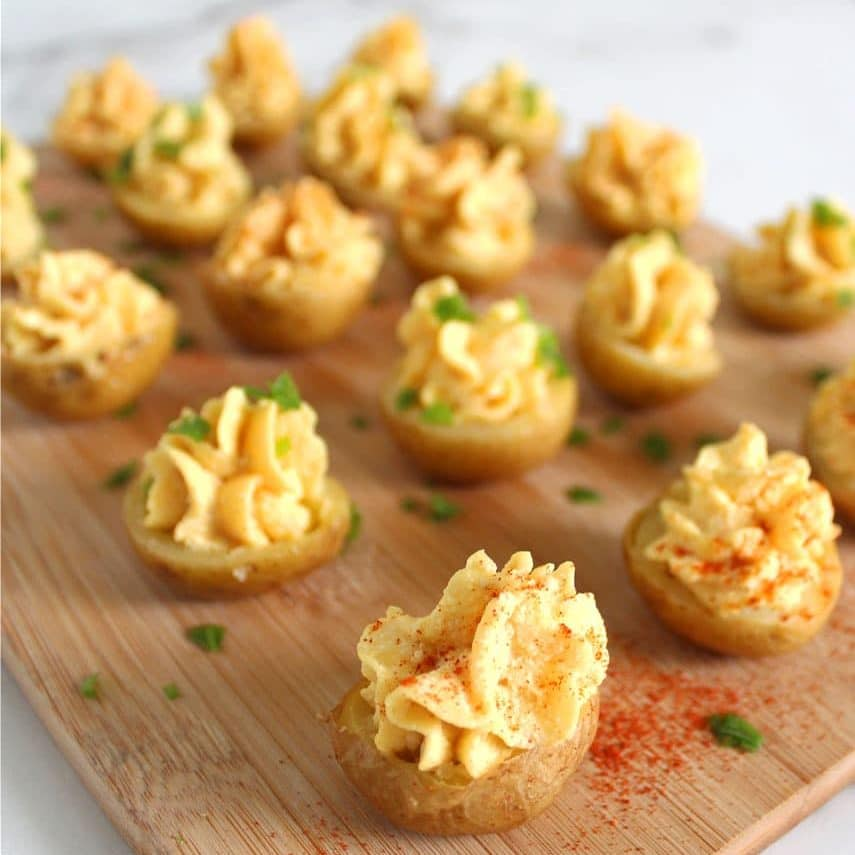 Picture of 16 vegan deviled eggs made in mini potatoes with paprika and green onion sprinkled on top