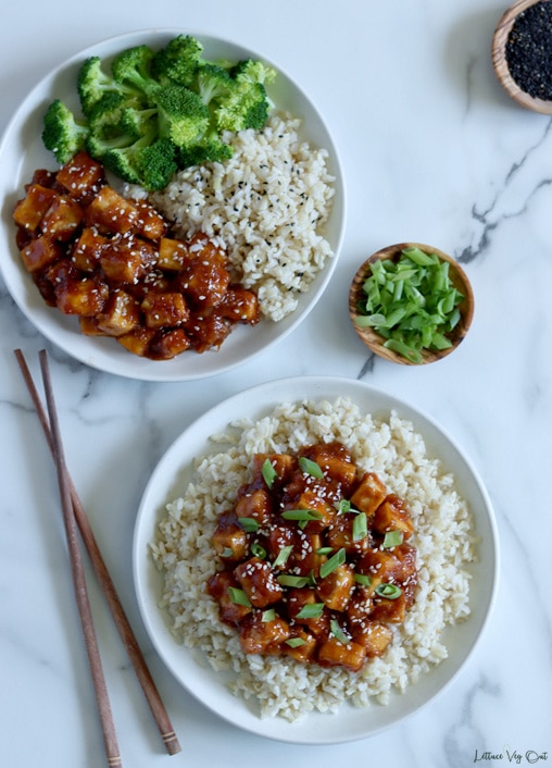 Top view of two plates of General Tso tofu; the bottom plate has the tofu piled over a bed of rice and the top plate has the tofu on a third of the plate with a third rice and a third broccoli. Wood chopsticks rest to the left of the bottom plate, on a white-grey marble background. Small wood bowl of green onion between the plates to the right.