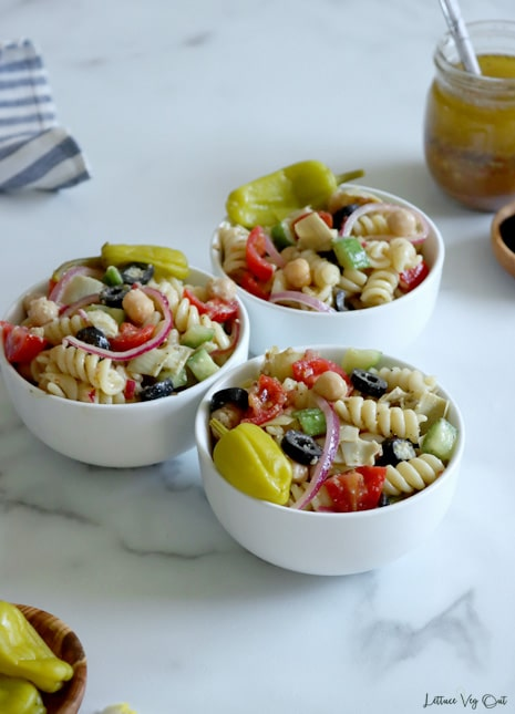 Three small white bowls filled with Italian pasta salad on white-grey marble. Small wood dish of pepperoncini peppers in bottom left corner with white blue striped towel in top left corner. Along right side of image is small jar of salad dressing with spoon in it and a mostly cropped out wood dish of olives.