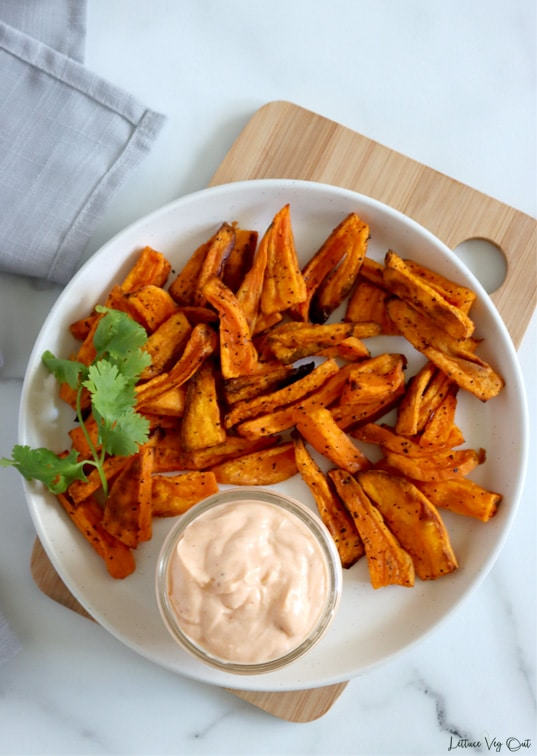 Top view of a plate of sweet potato fries with small dish of sriracha mayo dipping sauce on the plate. Plate sits on small wood board over white-grey marble with a bit of a light grey towel in top left corner.