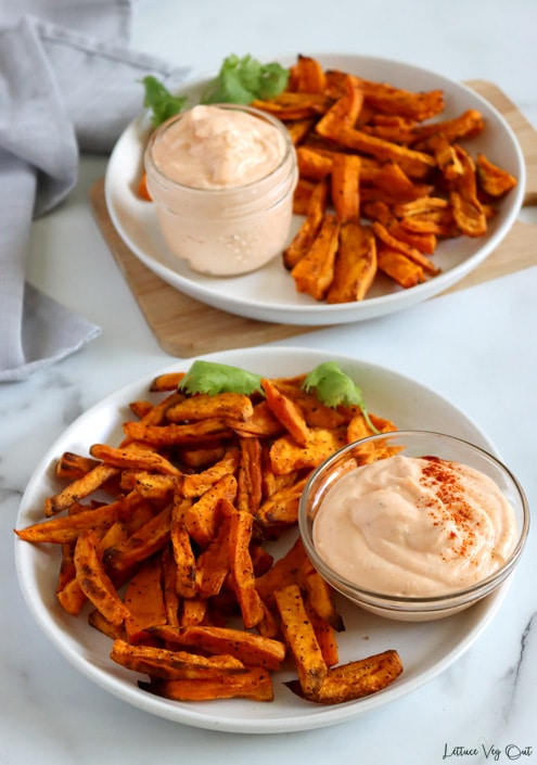 Two plates of sweet potato fries with small dishes of spicy mayo dipping sauce on the plate. Plates garnished with cilantro sprig. Back plate sits on wood board.