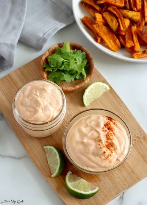 Top view of two glass dishes filled with sriracha mayo dip sitting on wood board along with lime wedges and small wood bowl of cilantro. Sweet potato fries in top right corner, largely cropped out.