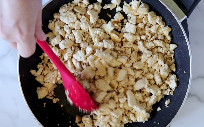 Top view of a hand holding a large red spoon and tossing lightly browned crumbled tofu around in a pan. The spoon and nearby tofu pieces are blurred in motion.