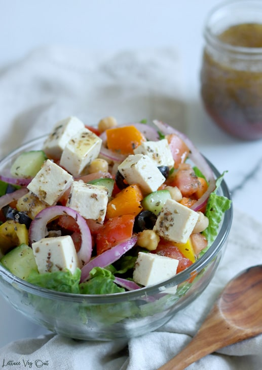 Glass bowl filled with un-tossed Greek salad (chopped lettuce at bottom, chopped vegetables on that with cubed tofu feta over the top). Bowl sits on light brown towel with wood spoon to the right and a jar of Greek dressing in a jar in the back right corner of image.