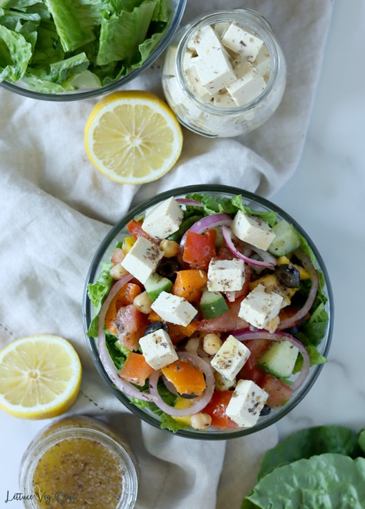 Top view of a glass bowl of Greek salad topped with cubes of tofu feta cheese. Above the bowl is a jar of tofu feta, half a lemon and a bowl of chopped lettuce. Below to the bowl of salad is another half lemon, jar of Greek dressing and the top of a Romaine lettuce leaf.