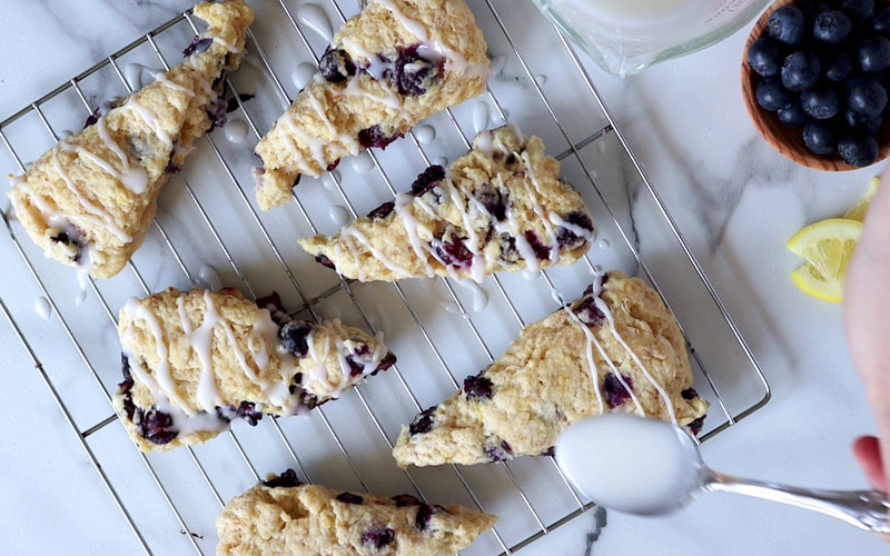 Top view of 6 cooked blueberry scones on a wire cooling rack over a white-grey marble counter. From the right side of image, a hand holding a spoonful of white icing is drizzling the icing over the scone on the bottom right of the cooling rack. The other scones already have a drizzle of glaze.
