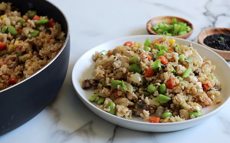 Cooked tofu fried rice on a plate, topped with green onion and black sesame seeds with small wood dishes of green onion and black sesame seeds to the back right and a large black pan filled with fried rice partially cropped out to the left of the image.