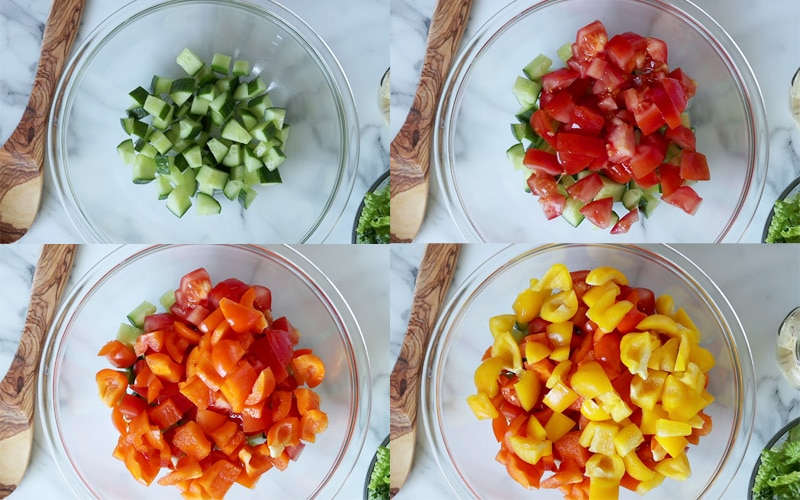 Compilation of 4 images each showing a top down view of a large glass bowl with a wood spoon to the left. From the top left, working right then down: bowl with just chopped cucumber in it; chopped tomato added on top of the cucumber; chopped orange bell pepper added on top of the tomato; chopped yellow bell pepper added on top of the orange pepper.