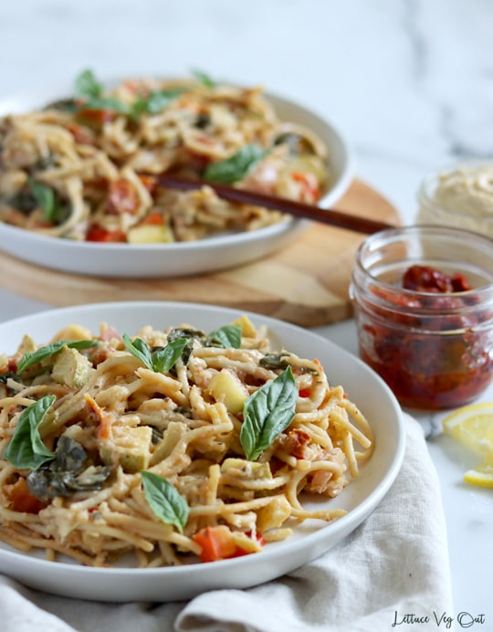 Front of view of a plate of spaghetti pasta with colorful vegetables, coated in creamy hummus pasta sauce and topped with fresh basil leaves that sits on a light brown towel. A second plate, with a wood fork in the pasta, sits to the back, elevated on a wood board. Small jar of sun dried tomato and second jar of hummus sit to the right, between the plates.