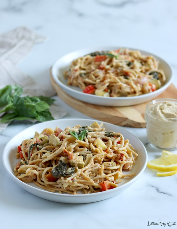 Two plates of spaghetti and vegetables coated in hummus pasta sauce with the front plate on white-grey marble background and back plate on a wood board. Jar of hummus and lemon slices to the right of image, between the plates with a folded towel and basil sprig to the left.