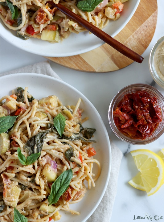 Top view of a plate of cooked hummus pasta with vegetables, garnished with fresh basil leaves. Plate sits on a folded light brown towel with a bit of a second plate, sitting on a wood board, visible along the top of the image but mostly cropped out. A jar of sun dried tomatoes and two lemon slices sit to the center right of image, next to the plate of hummus pasta.
