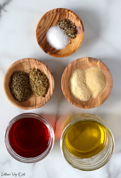 Top view of three small wood plates and two small glass jars filled with ingredients. From top working right then down: salt and pepper, dry oregano and basil, garlic powder and onion powder, red wine vinegar, olive oil.