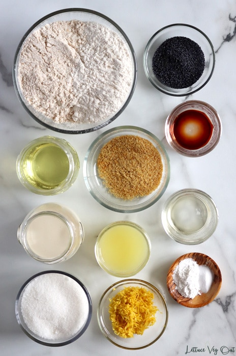 Top view of glass bowls and jars each filled with different ingredients. From top left going across then down: Flour, poppy seeds, vanilla extract, oil, ground flaxseed, soy milk, lemon juice, apple cider vinegar, sugar, lemon zest, baking soda and powder.