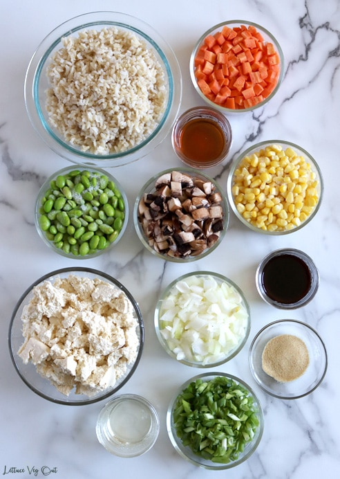 Top view of an arrangement of ingredients in glass bowls or jars on white-grey marble. From top left, working right then down: Cooked brown rice, raw chopped carrot, sesame oil, frozen shelled edamame, chopped raw mushroom, frozen corn, crumbled tofu, chopped raw white onion, soy sauce, garlic powder, mirin, chopped raw green onion.