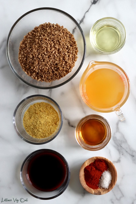 Top view of an arrangement of ingredients in glass bowls or jars on white-grey marble. From top left, working right then down: TVP, vegetable oil. vegetable broth, nutritional yeast, maple syrup, soy sauce, paprika and salt in same dish.