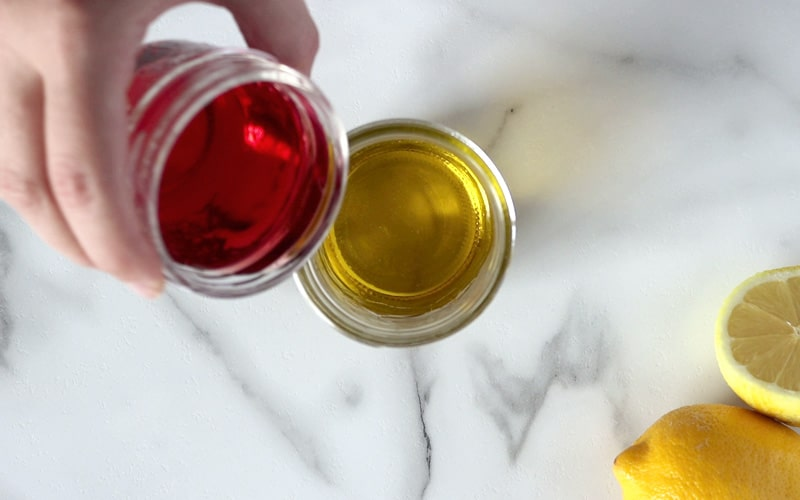 A hand holds a small jar filled with red wine vinegar that is being poured into another jar that is filled with olive oil. White-grey marble background with a whole and half lemon in bottom right corner.