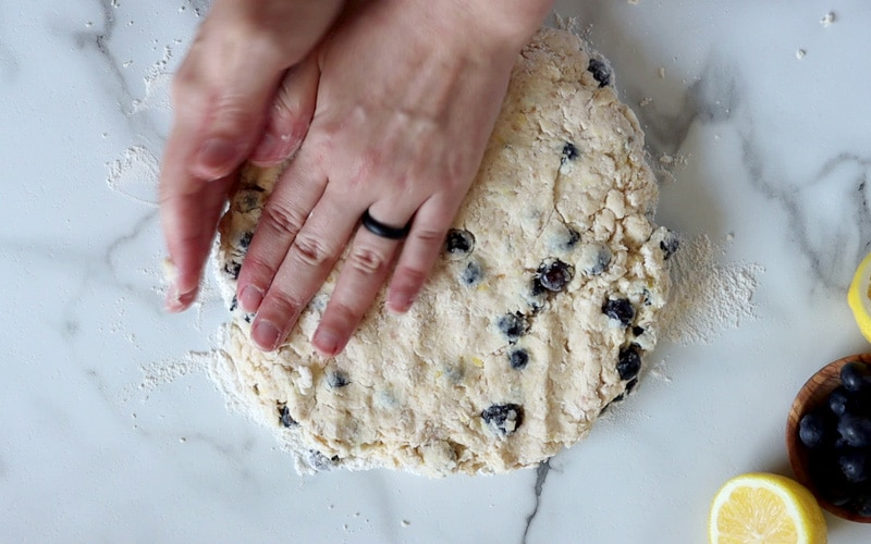 A flat, round disk of scone dough, filled with blueberries is being shaped by two hands; one hand is flat on top of the dough, in the top right corner, while the other is pressing along the edge of the dough to create a circle shape.