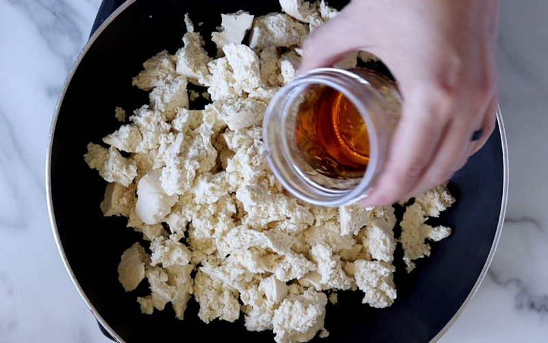 Hand holding a small jar of sesame oil over a pan filled with raw, crumbled tofu.