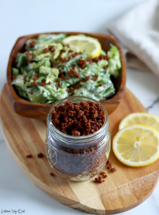 Small jar of TVP bacon bits sitting on an oval wood board along with two slices of lemon to the left and a square wood bowl of tossed Caesar salad topped with bacon bits behind the jar.