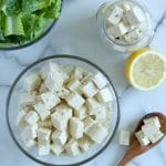 Square cropped image of the top view of a glass bowl of tofu feta cheese cubes sitting on a white-grey marble background. To the right is a wood spoonful of tofu feta and above that a half lemon and jar of tofu feta. Top left corner shows a quarter of a bowl of chopped lettuce.