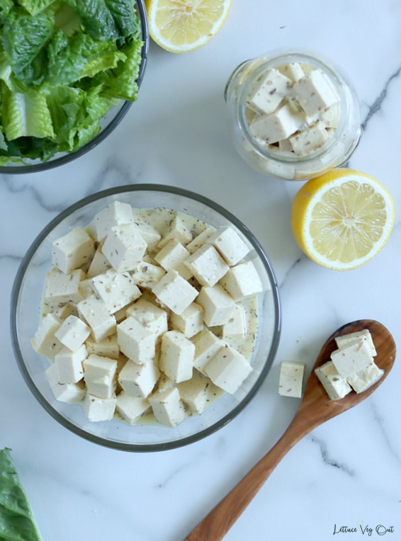 Top view of a glass bowl of tofu feta cheese cubes sitting on a white-grey marble background. To the right is a wood spoonful of tofu feta and above that a half lemon and jar of tofu feta. Top left corner shows a quarter of a bowl of chopped lettuce.
