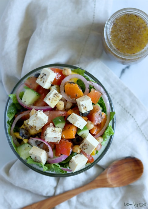 Top view of a glass bowl filled with prepared Greek salad (lettuce, vegetable mix, cubes of feta cheese all tossed in dressing). Bowl sits on crumpled light brown towel with a wood spoon below it and a jar of Greek dressing in the top right corner.