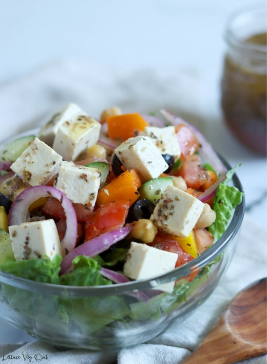 Close up of a glass bowl filled with Greek salad (chopped lettuce topped with a vegetable mix of cucumber, tomato, bell pepper, red onion, black olives and chickpeas all tossed in dressing and topped with cubes of tofu feta cheese). A blurred jar of salad dressing sits in back right corner of image.