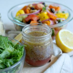 Square cropped image of a glass jar filled with Greek salad dressing sitting on light wood board with a glass bowl of chopped lettuce to the left of the jar. A second glass bowl filled with colorful chopped vegetables sits off the wood board behind the jar of dressing, sitting on a white-grey marble background