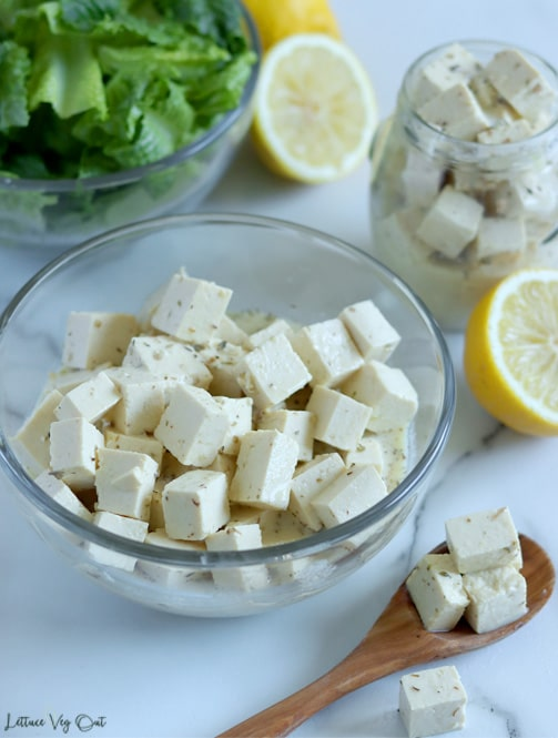 Glass bowl filled with cubes of marinated tofu feta cheese with a wood spoon of feta to the right. Along the top edge of the image, from left to right, are: a bowl of chopped lettuce, lemon half, jar of marinating tofu cubes, another half lemon.