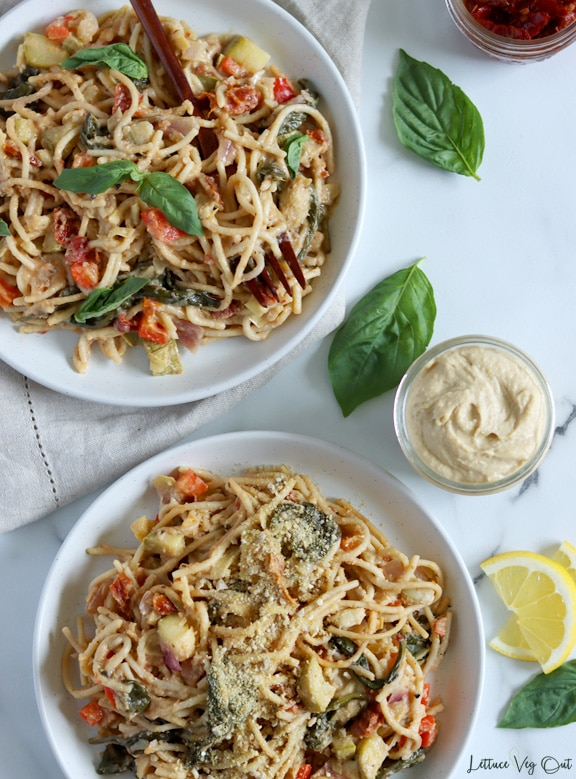 Two plates of vegetables and spaghetti cooked in hummus pasta sauce. Bottom plate garnished with vegan Parmesan and top plate garnished with basil leaves. Right side of image decorated with basil leaves and a small jar of hummus.