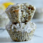 Square cropped image of a stack of two lemon poppy seed muffins with drizzled glaze over them with the top muffin having a large bite taken from it. Blurred muffins and lemons in the background.