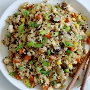 Square cropped image of a close up of the top view of a white plate filled with tofu fried rice with carrot, corn, mushrooms, edamame, green onion and black sesame seeds. Light wood chopsticks sit on the right edge of plate.