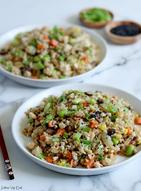 Straight on view of two white plates of vegan fried rice filled with carrot, corn, mushrooms, edamame and tofu with green onion and black sesame seed garnish. Two small wood bowls sit blurred in the back right of image (on with green onion and the other black sesame seeds).