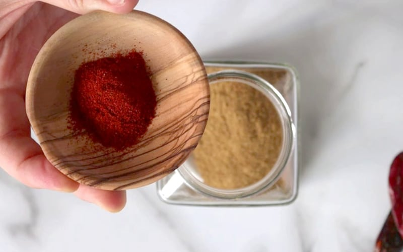 Top view of a small wood dish with bright red paprika in it, held up over a square glass jar that is slightly blurred and filled with a brown-colored spice. White-grey marble background.