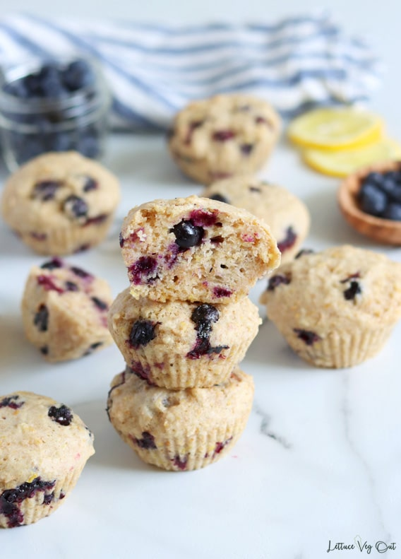 More top-down view of a stack of 3 blueberry lemon muffins, with the top muffin cut in half, showing the inside. Additional muffins are arranged randomly around the stack along with a small wood dish of blueberries on the right and small jar of blueberries on the left. A couple lemon slices and a white and blue stripped towel sit blurred in the background.