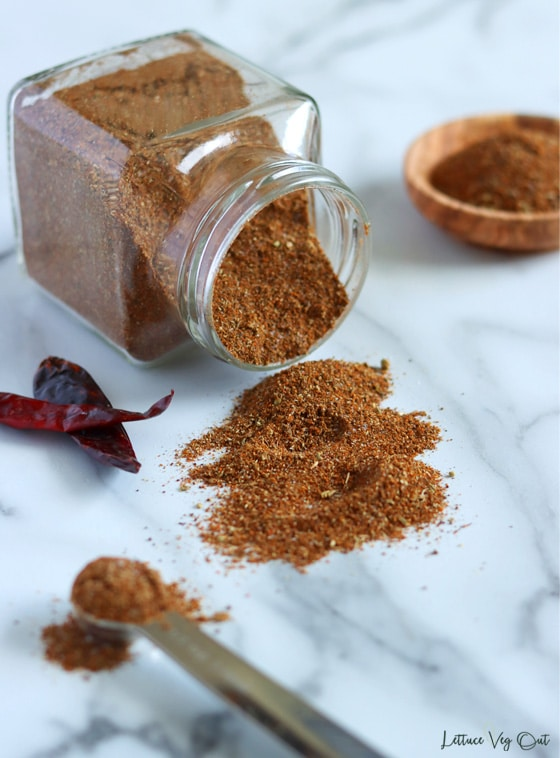 Square glass jar filled with taco seasoning mix tipped on it's side with seasoning spilling out onto the marble countertop below. Two dry red chillies to the left along with a metal measuring spoonful of seasoning in bottom left corner. Small wood bowl filled with seasoning in top right corner.