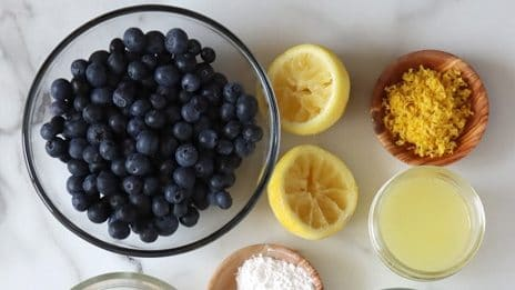 Top view of an arrangement of ingredients in glass or wood dishes sitting on white-grey marble. From top left working right then down: blueberries; lemon zest; lemon juice; ground flaxseed; baking powder and soda in same wood dish; sugar; oil; vanilla extract; plant-based milk; flour (half white and half whole wheat)