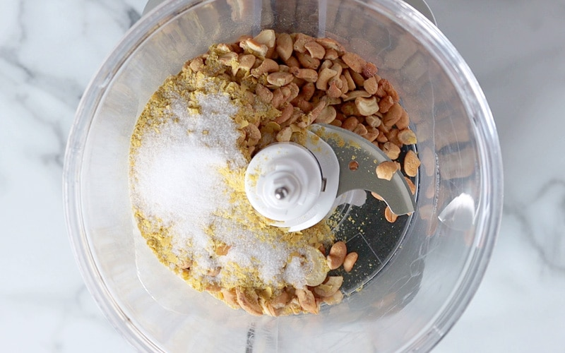 Top view of a food processor filled with cashew pieces along, nutritional yeast and salt.