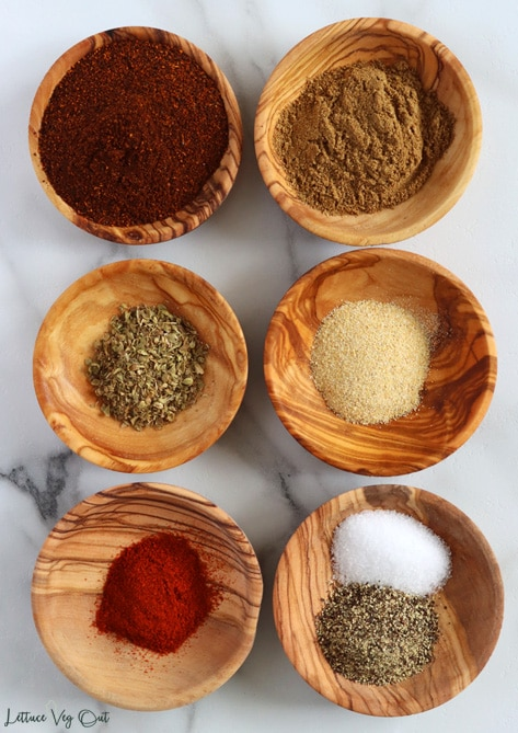Top view of 6 small wood dishes each filled with spices. From top left working right and down: chili powder, ground cumin, oregano, garlic powder, smoked paprika, salt and pepper (in same dish).