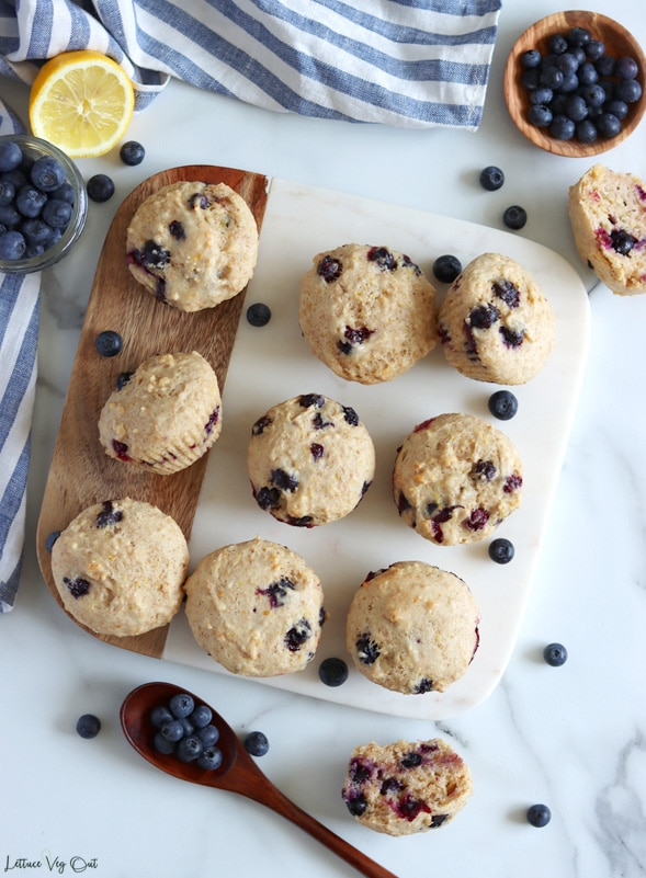 Top view of a square half marble and half wood board with 9 blueberry lemon muffins arranged in a messy manner on top. Board sits on a white-grey marble background with different ingredients decorating around it (white and blue stripped towel along top and left; jar of blueberries and half lemon in top left; spoonful of blueberries and half a muffin in bottom; wood dish of blueberries and half muffin in top right)