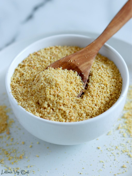Small white bowl filled with crumbly vegan parmesan cheese (ground cashews) with a wood spoon resting in the bowl. Bowl sits on plate with the parmesan dusted on the right and left side.