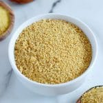 Square cropped image of a small white bowl filled with vegan cashew parmesan (golden brown-yellow crumbly mixture) sitting on white-grey marble.