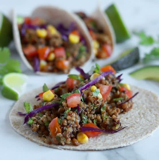 """Close up of an open taco that is filled with quinoa taco """"meat"""" and topped with tomato, corn, red cabbage and cilantro. Two other tacos that are folded sit blurred in the back along with lime wedges, avocado slices and cilantro garnishes."""
