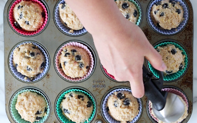 Top view of a hand holding a black and metal scoop and is dumping muffin batter into a silicone-lined muffin slot in the bottom right corner of image. Rest of image shows the remaining 11 slots of the muffin pan all filled with blueberry muffin batter in colorful silicone liners.