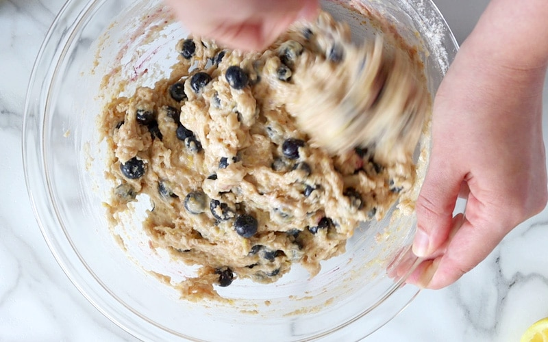 Top view of a blurry hand stirring muffin batter that is light brown in color and loaded with blueberries. The batter near the spoon is blurred, in motion while the rest of the batter is in focus and appears to be thick but without large clumps. A second hand hold the right edge of the mixing bowl.