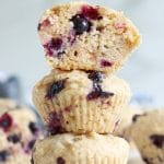 Square cropped image of a straight on shot of a stack of 3 blueberry lemon muffins with the top muffin cut in half, showing the inside. Additional muffins arranged and blurry in background.