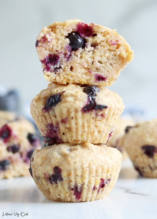 Straight on shot of a stack of 3 blueberry lemon muffins with the top muffin cut in half, showing the inside. Additional muffins arranged and blurry in background.